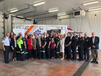 group of people standing in front of an ambulance