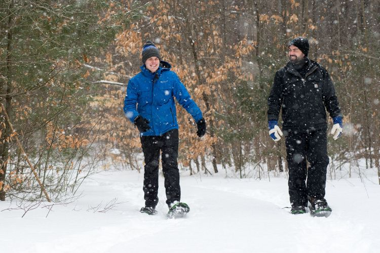 two people snowshoeing in forest